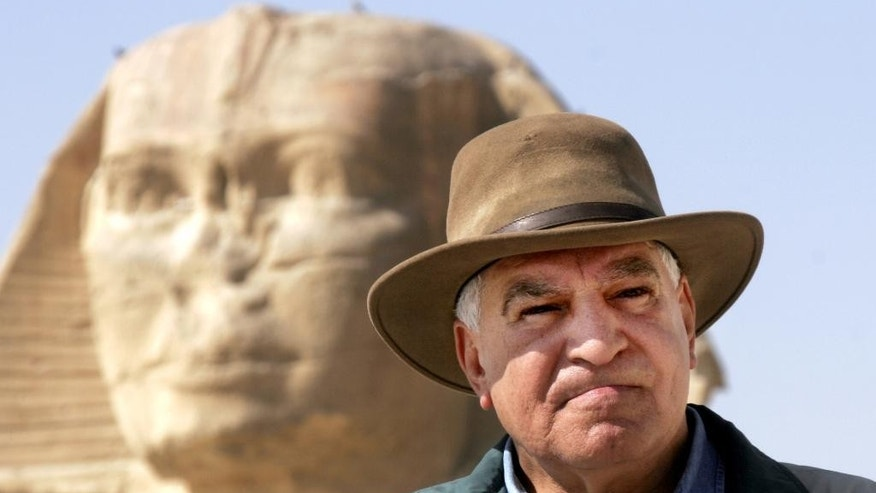 FILE -  In this file photo taken  March 11, 2007, Zahi Hawass, Egypt's former top antiquities official, poses in front of the ancient Sphinx in Giza, Egypt. Egypt's best-known archaeologist is a passionate showman with an explorer's fedora who joined the last, doomed Cabinet of President Hosni Mubarak, then resigned in a swirl of corruption allegations after the 2011 revolution ousted his patron. Admired or reviled, he is once again a frontman for Egypt, exhorting international audiences to see the heritage of a country where unrest has hit tourism hard.  (AP Photo/Amr Nabil, File)