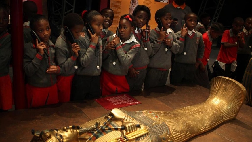 "In this photo taken Wednesday, Jan. 28, 2015, schoolchildren roam an exhibition of  replicas of Tutankhamun's treasures at an exhibition at a Krugersdorp, South Africa, Casino, brought to South Africa by Egypt's former top antiquities official Zahi Hawass. In an interview with the Associated Press, Hawass declared that ""Egypt is safe"" adding that antiquities sites are safe.' (AP Photo/Denis Farrell)"