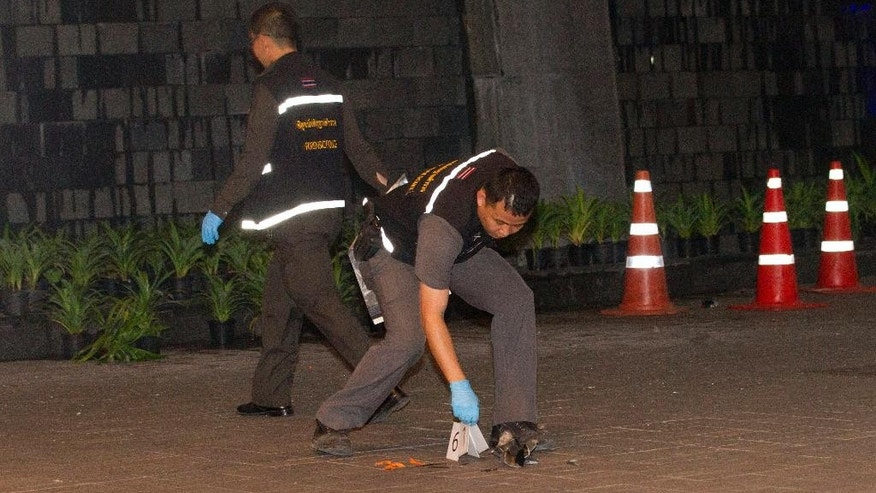 Thai police forensic officers investigate near the front of the Siam Paragon shopping mall, the site of a blast in Bangkok, Thailand, Sunday, Feb. 1, 2015. Thai police say that two explosions at a transit hub near major downtown shopping mall were caused by small improvised explosive devices, but no one was hurt and damage was minor.( AP Photo/Sakchai Lalit)