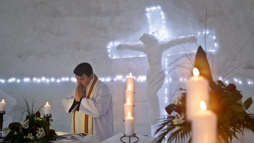 A Romanian priest prays inside a church built entirely from ice blocks cut from a frozen lake after a blessing religious service at the Balea Lac resort in the Fagaras mountains, Romania, Thursday, Jan. 29, 2015. The blessing was performed jointly by priests from all Christian denominations in Romania and the church, built at an altitude of over 2,000 meters, will host all types of religious events like weddings and baptizing ceremonies as long as the cold weather lasts.(AP Photo/Vadim Ghirda)
