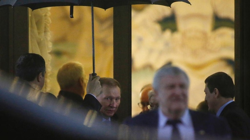 Former Ukrainian President Leonid Kuchma, center, leaves the talks in Minsk, Belarus, late Saturday, Jan. 31, 2015.  Talks on the eastern Ukraine settlement collapsed on Saturday as Ukrainian envoy Leonid Kuchma said that the pro-Russian rebels refused to discuss steps to bring a cease-fire to the war-torn region. (AP Photo/Sergei Grits)