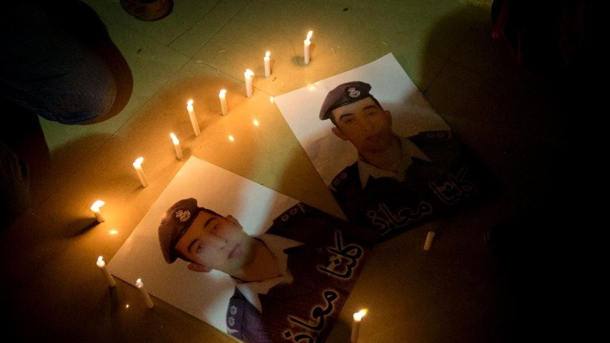 "Members of Al-Kaseasbeh, the tribe of Jordanian pilot, Lt. Muath al-Kaseasbeh, who is held by the Islamic State group militants, light candles by posters with his picture and Arabic that reads ""we are all Muath,"" at the captured pilot's tribal gathering divan, in his home town of Karak, Jordan, Saturday, Jan. 31, 2015. An online video released Saturday night purported to show an Islamic State group militant behead Japanese journalist Kenji Goto, ending days of negotiations by diplomats to save the man. (AP Photo/Nasser Nasser)"