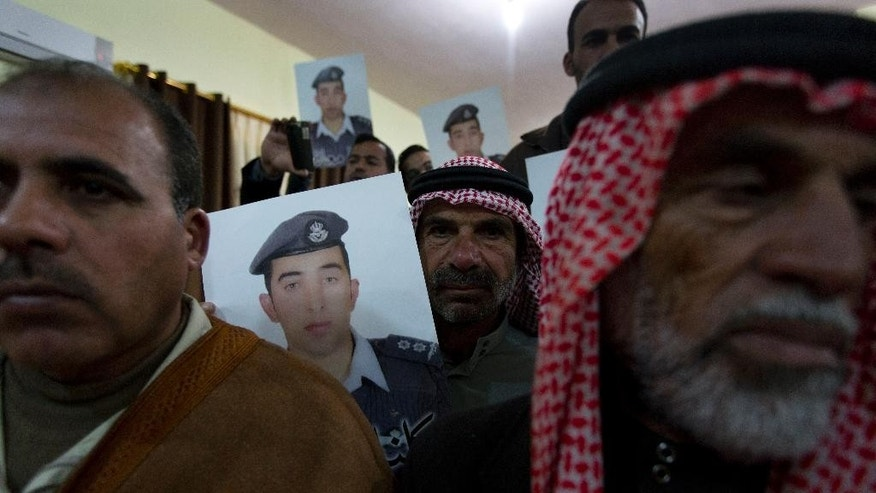 "Members of Al-Kaseasbeh, the tribe of Jordanian pilot, Lt. Muath al-Kaseasbeh, who is held by the Islamic State group militants, carry posters with his picture and Arabic that reads ""we are all Muath,"" at the captured pilot's tribal gathering divan, in his home town of Karak, Jordan, Saturday, Jan. 31, 2015.  An online video released Saturday night purported to show an Islamic State group militant behead Japanese journalist Kenji Goto, ending days of negotiations by diplomats to save the man. (AP Photo/Nasser Nasser)"