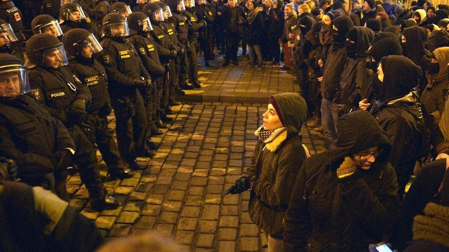 Policemen stand in front of anti PEGIDA demonstrators during a rally of the group Patriotic Europeans against the Islamization of the West, or PEGIDA, in Vienna, Austria, Monday, Feb. 2, 2015. (AP Photo/Hans Punz)