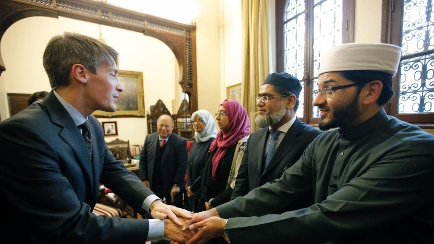 Thomas Andrieu, a top aide to the French Interior Minister, left, greets Qari Mohammed Asim MBE, Senior Imam At Leeds' Makkah Masjid, right, during a meeting at the Grand Central Mosque in Paris, France, Monday, Feb. 2, 2015. British Imams travel to Paris to meet with Muslim and Jewish leaders to stand together in solidarity against extremism. (AP Photo/Francois Mori)