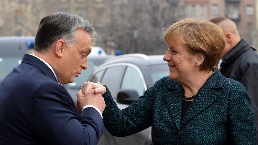 Hungarian Prime Minister Viktor Orban, left, greets German Chancellor Angela Merkel  in front of the Parliament building in Budapest, Hungary, Monday, Feb. 2, 2015. Angela  Merkel is staying in Hungary for  a one-day official visit. (AP Photo/MTI/Tibor Illyes)