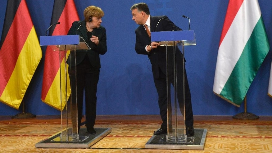 Hungarian Prime Minister Viktor Orban, right, and German Chancellor Angela Merkel attend a news conference after their meeting in the Parliament building in Budapest, Hungary, Monday, Feb. 2, 2015. Angela Merkel is staying in Hungary on a one-day official visit. (AP Photo/MTI/Tibor Illyes)