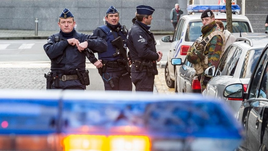 Policemen and a security officer stand outside a European Parliament building in Brussels on Monday, Feb. 2, 2015. Belgian police have evacuated hundreds of people from the European Parliament after a suspicious vehicle was spotted nearby. (AP Photo/Geert Vanden Wijngaert)