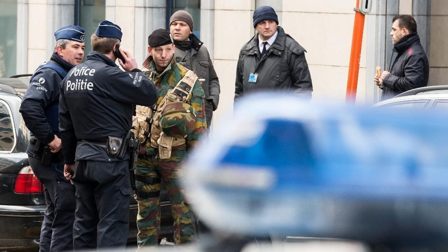 Policemen and security officers stands outside a European Parliament building in Brussels on Monday, Feb. 2, 2015. Belgian police have evacuated hundreds of people from the European Parliament after a suspicious vehicle was spotted nearby. (AP Photo/Geert Vanden Wijngaert)