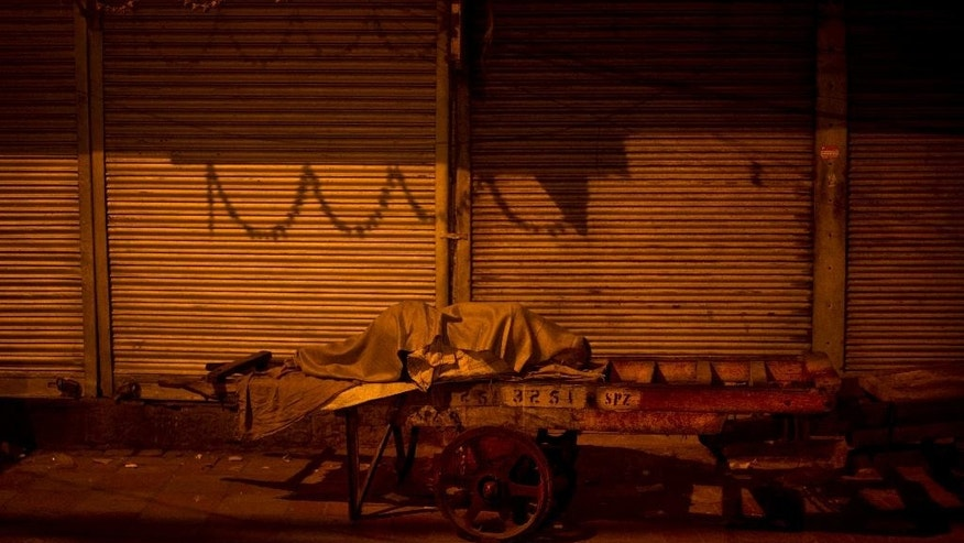 In this Wednesday, Nov. 12, 2014 photo, a cart puller sleeps at Khari Baoli, a wholesale spice market, in New Delhi, India. Of the thousands of migrant workers from across India that come to Delhi in search of jobs, many end up pulling or assisting the carts that are widely used to transport goods at Khari Baoli. (AP Photo/Saurabh Das)