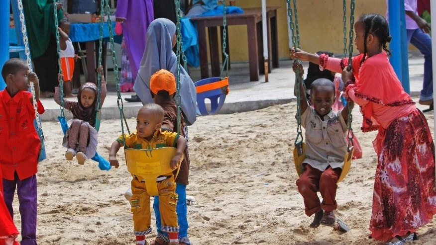 In this photo taken Saturday, Oct 4, 2014, Somali children play on swings at the Mogadishu Guest House, in Mogadishu, Somalia. The hotel has opened a children's playground and swimming pool in the hope of reshaping the lives of children in a city where decades of bloody battles have kept them indoors, their parents hiding them from violence, but where stability is increasing after the ouster of al-Shabab militants from the capital and surrounding towns. (AP Photo/Farah Abdi Warsameh)