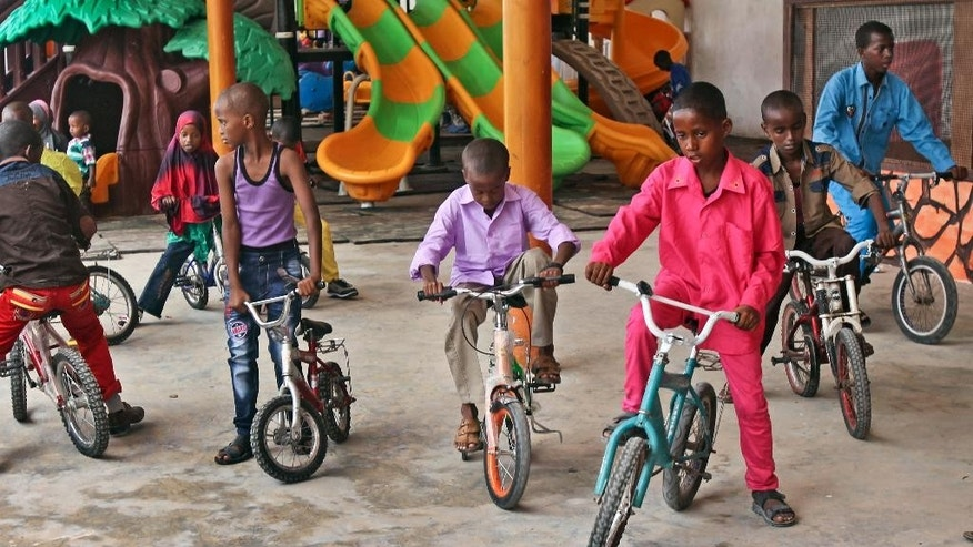 In this photo taken Saturday, Oct 4, 2014, Somali children ride bicycles at the Mogadishu Guest House, in Mogadishu, Somalia. The hotel has opened a children's playground and swimming pool in the hope of reshaping the lives of children in a city where decades of bloody battles have kept them indoors, their parents hiding them from violence, but where stability is increasing after the ouster of al-Shabab militants from the capital and surrounding towns. (AP Photo/Farah Abdi Warsameh)