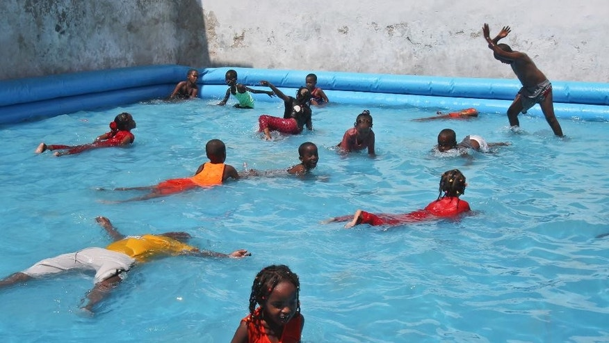 In this photo taken Saturday, Oct 4, 2014, Somali children splash around in a swimming pool at the Mogadishu Guest House, in Mogadishu, Somalia. The hotel has opened a children's playground and swimming pool in the hope of reshaping the lives of children in a city where decades of bloody battles have kept them indoors, their parents hiding them from violence, but where stability is increasing after the ouster of al-Shabab militants from the capital and surrounding towns. (AP Photo/Farah Abdi Warsameh)