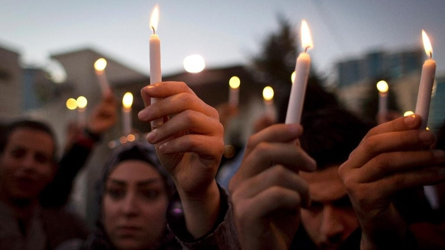 Jordanians hold candles during a candle vigil in support of Japan, in front of the Japanese embassy, in Amman, Jordan, Monday, Feb. 2, 2015. The wife of slain Japanese hostage Kenji Goto said Monday that she was devastated but proud of her husband, who was beheaded by Islamic State extremists. (AP Photo/Nasser Nasser)