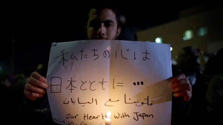 Jordanians carry banners and light candles during a candle vigil for Jordanians in support for Japan, in front of the Japanese embassy, in Amman, Jordan, Monday, Feb. 2, 2015. The wife of slain Japanese hostage Kenji Goto said Monday that she was devastated but proud of her husband, who was beheaded by Islamic State extremists. (AP Photo/Nasser Nasser)