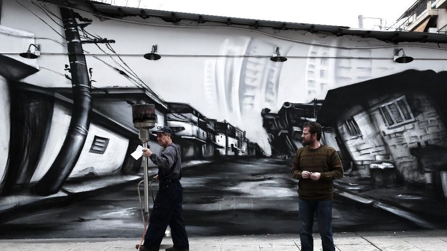 A workman carries an outdoor gas heater to be repaired past a mural in central Athens, on Monday, Feb. 2, 2015. Murals have exploded in run-down parts of the capital over the past five years of financial crisis, during which incomes have fallen at least 30 percent and more than a quarter of the workforce is jobless. Greece's new finance minister, Yanis Varoufakis, is continuing his tour of European capitals with a visit to London, after receiving backing from France for efforts to ease the terms of a 240 billion-euro ($270 billion) bailout.(AP Photo/Petros Giannakouris )