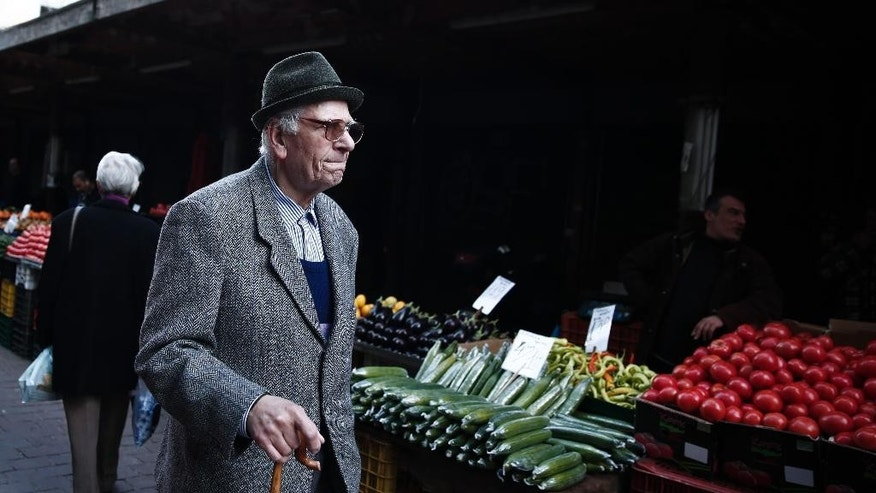 An elderly man carries a shopping bag as he walks in the central fruit and vegetable market in Athens, on Monday, Feb. 2, 2015. The  market has long appealed to low-budget shoppers, and is a favorite destination in a country where incomes have dropped at least 30 percent, amid record-high unemployment, during the past five years of acute financial crisis. Greece's new finance minister, Yanis Varoufakis, is continuing his tour of European capitals with a visit to London, after receiving backing from France for efforts to ease the terms of a 240 billion-euro ($270 billion) bailout.(AP Photo/Petros Giannakouris )