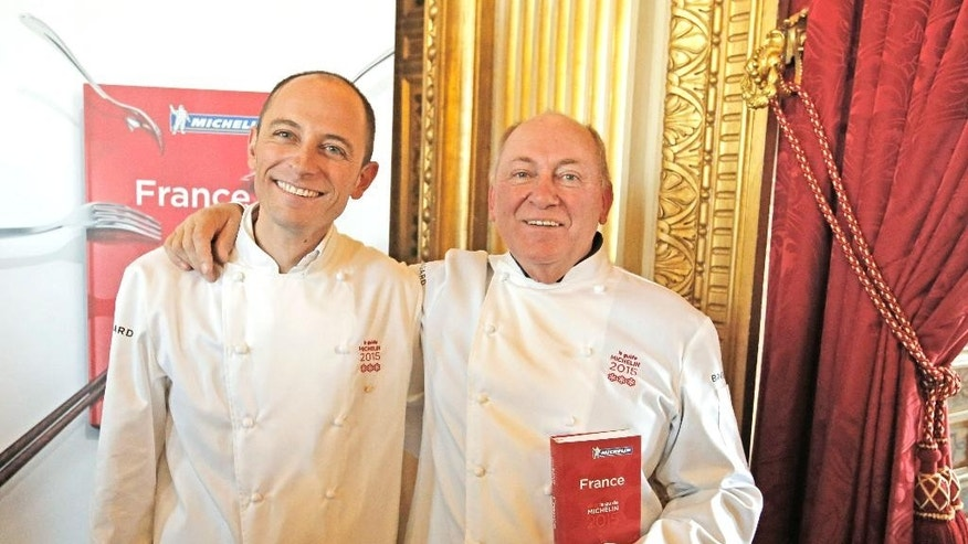 French chefs Rene, right, and his son Maxime Meilleur, who run La Bouitte restaurant in the French Alps, pose after being awarded three stars with the Michelin guide, Monday, Feb.2, 2015 in Paris. Two restaurants were newly awarded with the prestigious 3 stars this year. (AP Photo/Francois Mori)