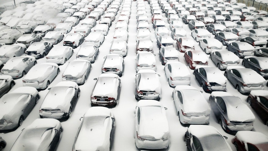 Cars are covered by snow in parking lot at O'Hare International Airport on Sunday, Feb. 1, 2015, in Chicago