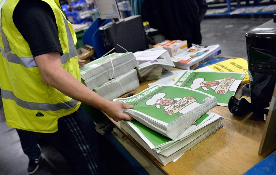 MARNE-LA-VALLEE, FRANCE - JANUARY 14:  A worker prepares the new edition of Charlie Hebdo for delivery in a press distribution center in the suburbs on January 14, 2014 in Marne-la-Vallee, France. Three million copies of the controversial magazine have been printed in the wake of last week's terrorist attacks. A second delivery of the magazine is scheduled for tomorrow.  (Photo by Aurelien Meunier/Getty Images)