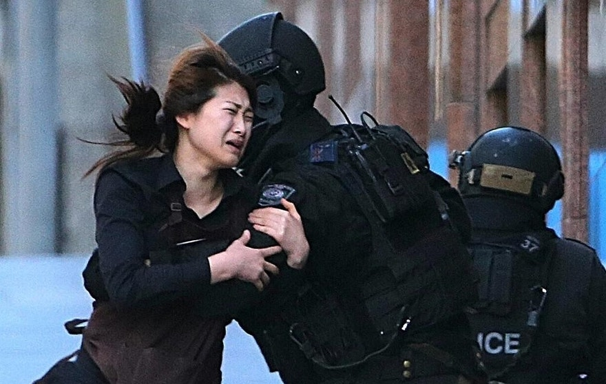 A hostage runs to armed tactical response police officers after escaping from a cafe under siege in Sydney, Australia. (AP Photo/Rob Griffith, File)