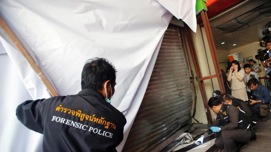 Thai police forensic officers investigate near an entrance to the Siam Paragon shopping mall in Bangkok, Thailand, Monday, Feb. 2, 2015. Police in Thailand on Monday were investigating a pair of bombings outside the luxury shopping mall in the heart of Bangkok, the first such violence reported in the capital since last year's army coup. (AP Photo/Sakchai Lalit)