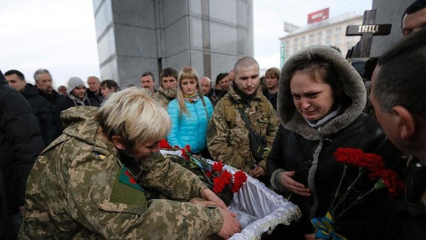 People pay their final respects to Ruslan Baburov  who was killed in fighting against Russian-backed separatists, during a commemoration ceremony in Independence Square in Kiev, Ukraine, on Monday, Feb. 2, 2015. Ukraine's government said Sunday that 13 of its troops were killed and another 20 wounded in a day of fighting across the east. (AP Photo/Sergei Chuzavkov)