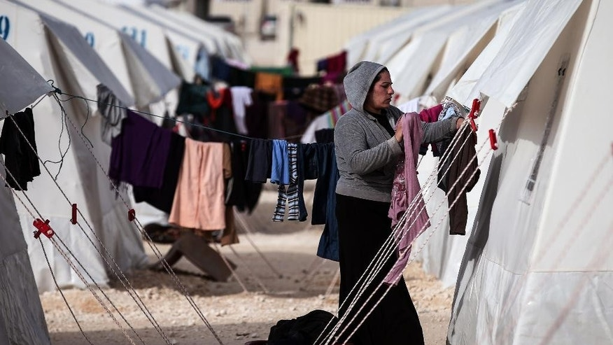 A Syrian refugee woman who fled violence in Syrian city of Ain al-Arab, known also as Kobani, hangs clothes outside her tent in a camp in the border town of Suruc, Turkey, Monday, Feb. 2, 2015. About 200,000 people arrived in Turkey since the start of fighting between Kurdish militia and Islamic State militants mid-September, 2014. (AP Photo/Emrah Gurel)