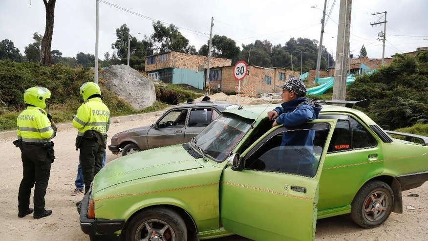 In this Jan. 15, 2015 photo, police check the ID's of unlicensed cabbies in Usme, on the outskirts of Bogota, Colombia. In Usme, unlicensed cabbies eke out a living shuttling residents up steep dirt roads where buses and regular taxis won't venture. For years each driver was forced to fork over about half their earnings to appease extortionists, but the criminal ring was dismantled in 2014 after a desperate cabbie secretly went to Colombia's elite Gaula police unit. (AP Photo/Fernando Vergara)