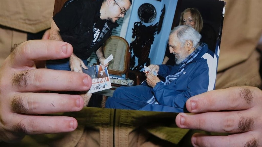 Student leader Randy Perdomo Garcia shows a picture of his meeting with Cuban leader Fidel Castro in Havana, Cuba, Tuesday Feb. 3, 2015. Cuba has published the first photos of Fidel Castro in five months, showing the 88-year-old former leader engaged in conversation with the head of the main Cuban student union. A first-person account by the student leader says the meeting took place on Jan. 23. The photos published around midnight on Monday are the first images of the revolutionary leader since a set of photos came out in August showing him talking with Venezuelan President Nicolas Maduro. (AP Photo/Desmond Boylan)