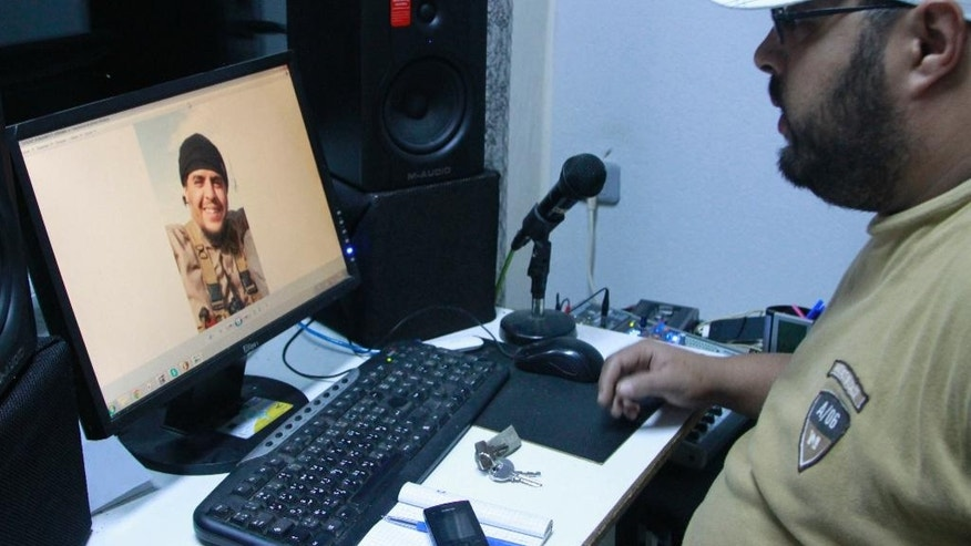 "In this Dec. 4, 2014 photo, Mehdi ""DJ Costa"" Akkari, a Tunisian rapper, looks at an image of his brother Youssef, who fought with extremists in Syria and was killed by a U.S. airstrike, in Tunis, Tunisia. While foreigners from across the world have joined the Islamic State militant group, some arrive in Iraq or Syria only to find day-to-day life much more austere and violent than they had expected. (AP Photo/Paul Schemm)"