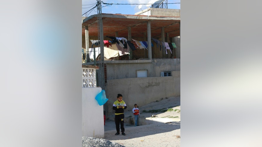 In this Dec. 5, 2014 photo, a young boy uses a plastic bag like a balloon in the low-income Tunis suburb of Mhamdiya, Tunisia, which has produced a number of young men that left to fight in Syria for extremist groups. While foreigners from across the world have joined the Islamic State militant group, some arrive in Iraq or Syria only to find day-to-day life much more austere and violent than they had expected. These disillusioned new recruits soon discover that it is a lot harder to leave the Islamic State than to join. (AP Photo/Paul Schemm)