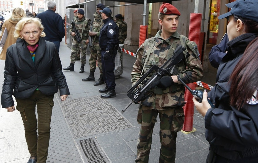 Soldiers and police officers stand guard after an attacker with a knife hidden in his bag attacked three soldiers on an anti-terror patrol in front of a Jewish community center in Nice, southern France, Tuesday Feb. 3, 2015. France has been on high alert since the attacks in the Paris region by three Islamic extremists that left 20 people dead, including the gunmen. More than 10,000 soldiers have been deployed around the country to protect sensitive locations, including major shopping areas, synagogues, mosques and transit hubs. (AP Photo/Lionel Cironneau)