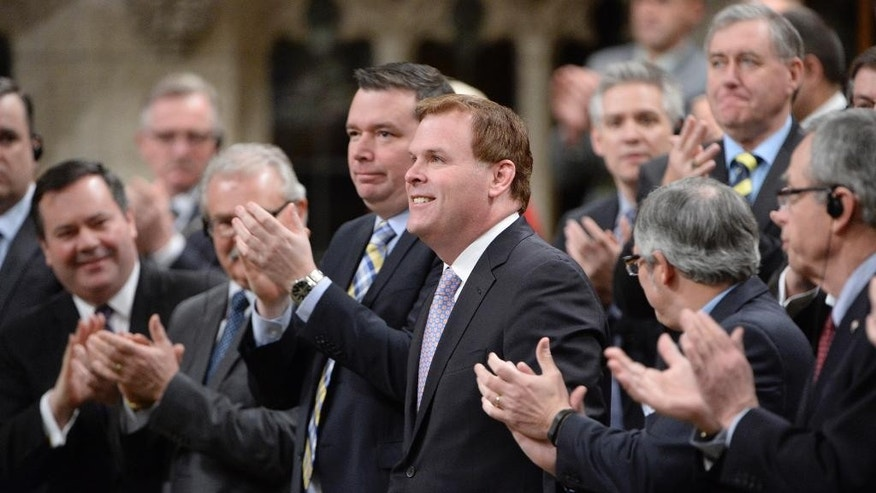 Canada's Foreign Minister John Baird receives a standing ovation in the House of Commons in Ottawa on Tuesday, Feb. 3, 2015.  Baird announced his resignation from the Cabinet on Tuesday. (AP Photo/The Canadian Press, Adrian Wyld)
