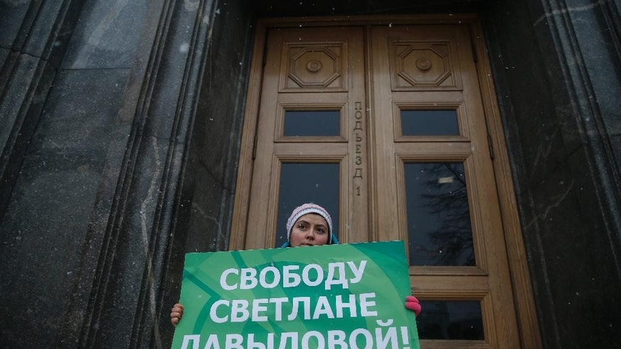 An unidentified member of liberal Yabloko Party holds a placard in support of  Svetlana Davydova outside the FSB (Federal Security Service) headquarters in Moscow, Tuesday, Feb. 3, 2015. Davydova, a mother of seven who lives in the city of Vyazma in western Russia, was arrested in January on treason charges for providing Ukraine with information on Russian troops movements. Rights defenders and opposition activists have rejected charges against her as unfounded and absurd. The poster reads: Freedom to Svetlana Davydova. (AP Photo Pavel Golovkin)