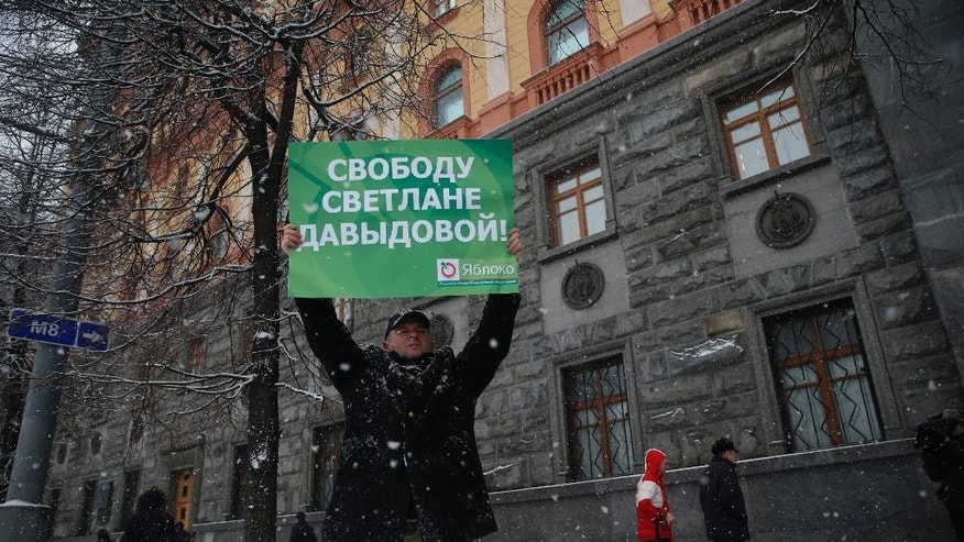 An unidentified member of liberal Yabloko Party holds a placard in support of  Svetlana Davydova outside the FSB (Federal Security Service) headquarters in Moscow, Tuesday, Feb. 3, 2015. Davydova, a mother of seven who lives in the city of Vyazma in western Russia, was arrested in January on treason charges for providing Ukraine with information on Russian troops movements. Rights defenders and opposition activists have rejected charges against her as unfounded and absurd. The poster reads: Freedom to Svetlana Davydova. (AP Photo/Pavel Golovkin)