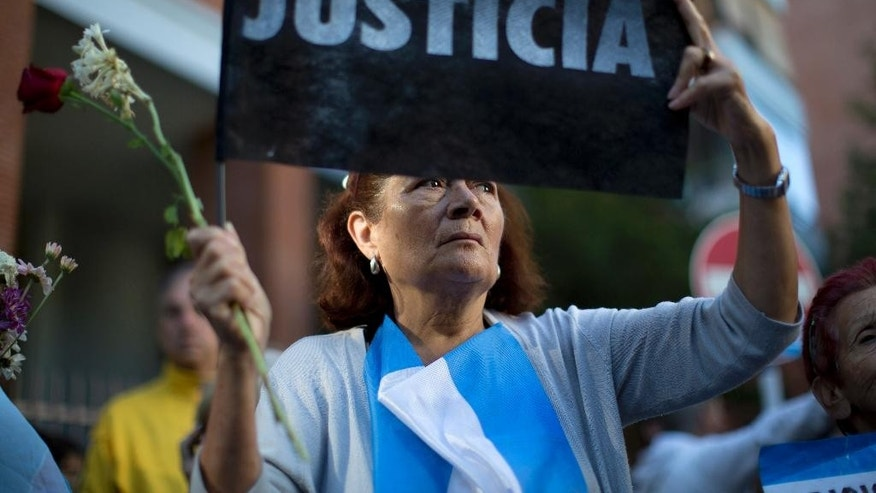 "In this Thursday, Jan. 29, 2015 photo, a woman holds up a sign that reads in Spanish ""Justice"" as she gathers with others outside the funeral home where a private wake for the late prosecutor Alberto Nisman takes place, in Buenos Aires, Argentina. Nisman was scheduled to appear before Congress the day after he was found dead in his apartment on Jan. 18, to detail his allegations that President Cristina Fernandez had conspired to protect some of the Iranian suspects in the 1994 bombing of a Jewish center. The man who gave Nisman the gun that killed him said Wednesday that Nisman feared for the safety of his daughters and didn't trust the policemen protecting him. (AP Photo/Rodrigo Abd)"
