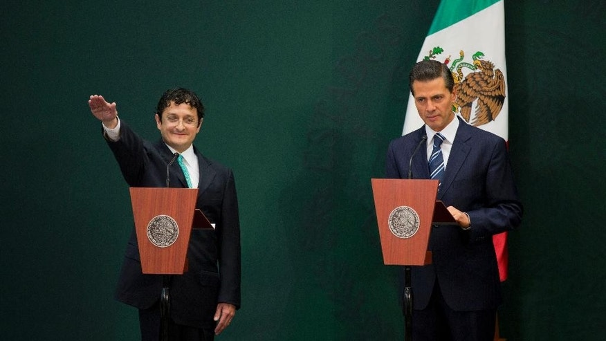Virgilio Andrade Martinez, left, is sworn-in as the Secretary of Public Administration by Mexican President Enrique Pena Nieto, during a press conference in Mexico City, Tuesday, Feb. 3, 2015. Pena Nieto said Tuesday he has asked the Public Administration Department to investigate the purchases of luxury homes, by himself, his wife and his finance secretary, from government contractors. (AP Photo/Rebecca Blackwell)