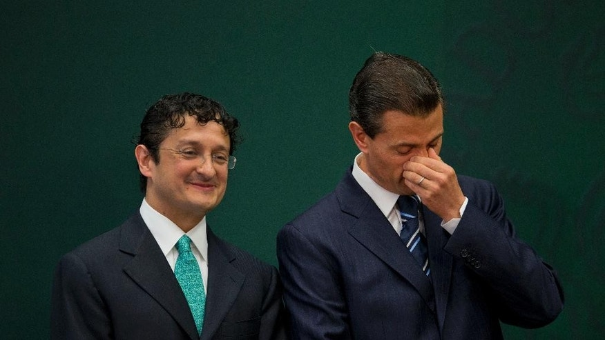 Mexican President Enrique Pena Nieto, right, stands with Virgilio Andrade Martinez, during a press conference to announce Andrade's appointment as the Secretary of Public Administration, in Mexico City, Tuesday, Feb. 3, 2015. Pena Nieto said Tuesday he has asked the Public Administration Department to investigate the purchases of luxury homes, by himself, his wife and his finance secretary, from government contractors. (AP Photo/Rebecca Blackwell)