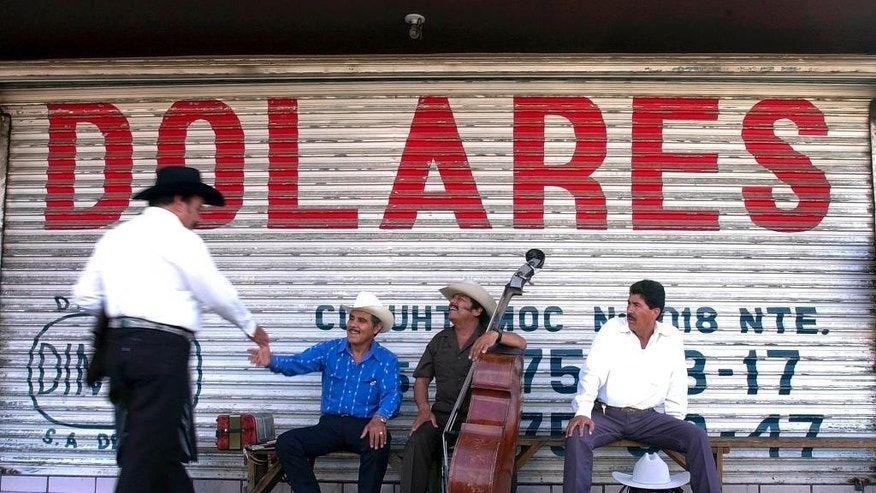 "FILE - In this June 25, 2002 file photo, Northern Mexican musicians who play ""Norteno"" music greet each other as they wait for clients under a sign that reads ""dollars"" in Spanish in Monterrey, Mexico. Mexico's central bank says remittances sent home by Mexicans living abroad rebounded in 2014 after falling the previous year. Money sent home by Mexicans are one of the country's main sources of foreign income, along with oil exports. (AP Photo/Gregory Bull, File)"