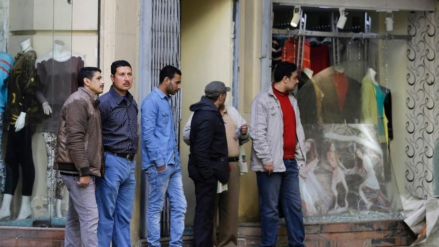 Egyptians inspect damages after a flash-bang grenade exploded in downtown Cairo, Egypt, Tuesday, Feb. 3, 2015. A flash-bang grenade planted inside an electrical box in an open-air commercial arcade in downtown Cairo exploded, panicking passers-by, but causing no injuries. (AP Photo/Hassan Ammar)