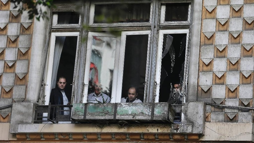 Egyptian men inspect damages after a flash-bang grenade exploded in downtown Cairo, Egypt, Tuesday, Feb. 3, 2015. A flash-bang grenade planted inside an electrical box in an open-air commercial arcade in downtown Cairo exploded, panicking passers-by, but causing no injuries. (AP Photo/Hassan Ammar)