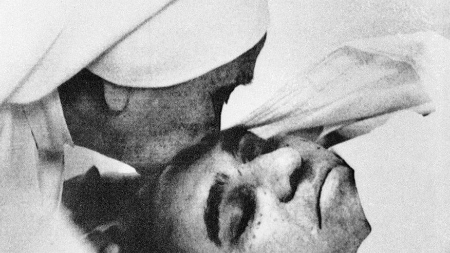 FILE - In this March 23, 1980, file photo, a nun plants a kiss on the forehead of Archbishop Oscar Arnulfo Romero of El Salvador at the Hospital of Divine Providence. Pope Francis decreed Tuesday, Feb. 3, 2015, that the slain Salvadoran Archbishop was killed in 1980 out of hatred for his Catholic faith, approving a martyrdom declaration that sets the stage for his beatification. (AP Photo, File)