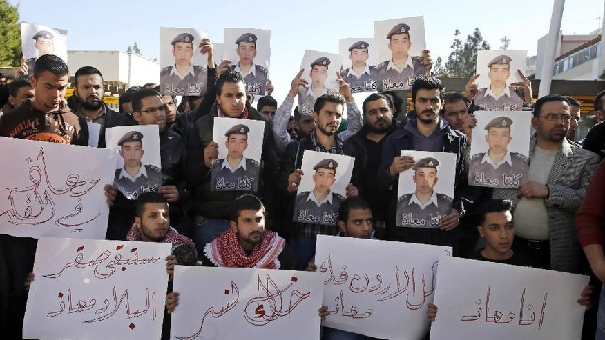 "Supporters of Jordanian pilot, Lt. Muath al-Kaseasbeh, who is held by Islamic State group militants, hold posters of him with Arabic that reads, ""we are all Muath,"" during a protest in Amman, Jordan, Tuesday, Feb. 3, 2015. Al-Kaseasbeh was seized after his F-16 jet crashed near the Islamic State group's de facto capital, Raqqa, Syria, in December last year. (AP Photo/Raad Adayleh)"