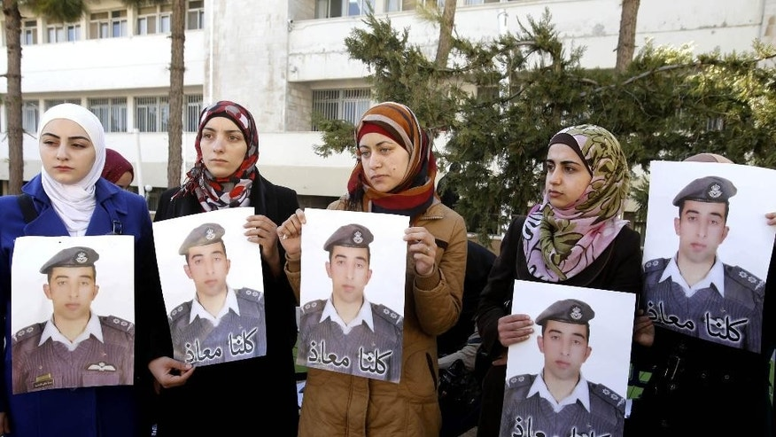 "Anwar al-Tarawneh, center, the wife of Jordanian pilot, Lt. Muath al-Kaseasbeh, who is held by Islamic State group militants, holds a posters of him with Arabic that reads, ""we are all Muath,"" during a protest in Amman, Jordan, Tuesday, Feb. 3, 2015. Al-Kaseasbeh was seized after his F-16 jet crashed near the Islamic State group's de facto capital, Raqqa, Syria, in December last year.  (AP Photo/Raad Adayleh)"