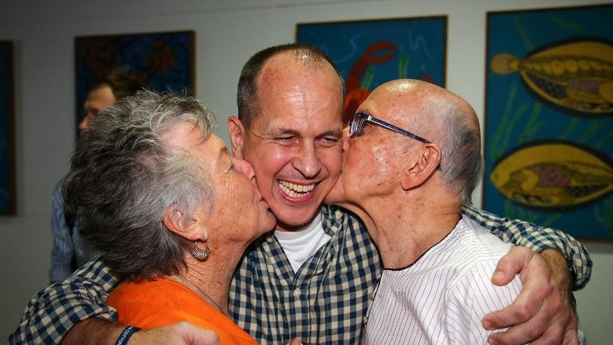 Australian journalist Peter Greste is hugged by his mother Lois, left, and father Juris, right, after his arrival in Brisbane, Australia, Thursday, Feb. 5, 2015. Greste, a reporter for Al-Jazeera English was released from an Egyptian prison and deported after more than a year behind bars. (AP Photo/Tertius Pickard)