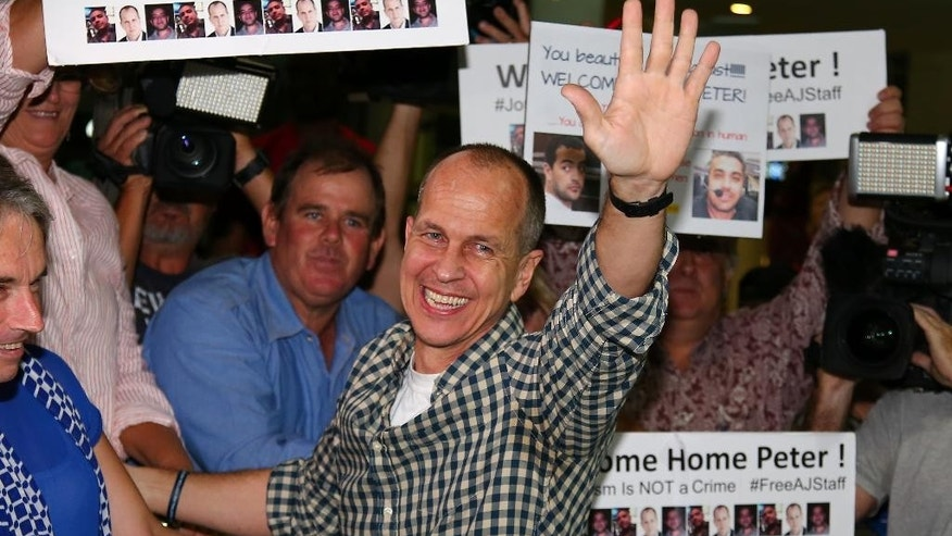Australian journalist Peter Greste waves to supporters after he arrived in Brisbane, Australia, Thursday, Feb. 5, 2015. Greste, a reporter for Al-Jazeera English was released from an Egyptian prison and deported after more than a year behind bars. (AP Photo/Tertius Pickard)
