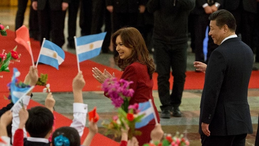 Argentine President Cristina Fernandez waves at Chinese children waving the Chinese and Argentine flags as she walks next to Chinese President Xi Jinping during a welcome ceremony at the Great Hall of the People in Beijing, Wednesday, Feb. 4, 2015. (AP Photo/Ng Han Guan)