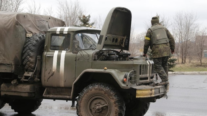Ukranian government soldiers tries to fix his truck in Artemivsk, Ukraine, Wednesday, Feb. 4, 2015.  Soldiers bark orders at exhausted residents boarding evacuation buses with overflowing bags in hand, as another rebel artillery attack pummels this town on the front lines of Ukraine's separatist war. Despair is deepening for a shrinking population that has been without power, heating and running water for almost two weeks. The relentless rebel advance on the  railway town of Debaltseve is being slowed only by Ukrainian tanks, cannons and rocket launchers. (AP Photo/Petr David Josek)