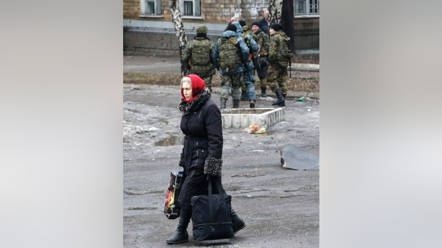 In this image taken Tuesday Feb. 3, 2015 a woman carries her belongings to a building used as an evacuation center in the town of Debaltseve, Ukraine. Soldiers bark orders at exhausted residents boarding evacuation buses with overflowing bags in hand, as another rebel artillery attack pummels this town on the front lines of Ukraine's separatist war. Despair is deepening for a shrinking population that has been without power, heating and running water for almost two weeks. The relentless rebel advance on the  railway town of Debaltseve is being slowed only by Ukrainian tanks, cannons and rocket launchers.  (AP Photo/Petr David Josek)
